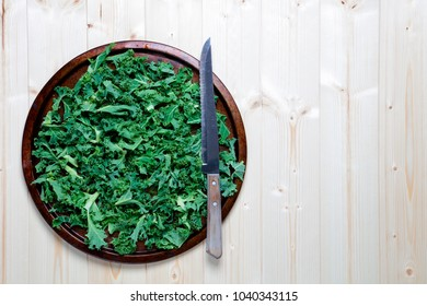 Fresh chopped prepared kale on old metal platter with knife