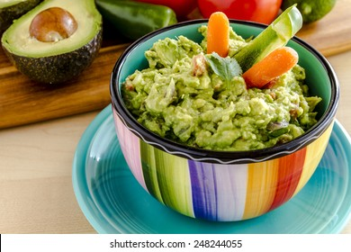 Fresh chunky guacamole in colorful bowl sitting on bright blue plate garnished with raw carrots and green peppers and cilantro