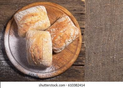Fresh ciabatta bread on cutting board, top view