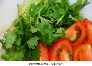 fresh cilantro leaf and chopped tomatoes on white chopping board