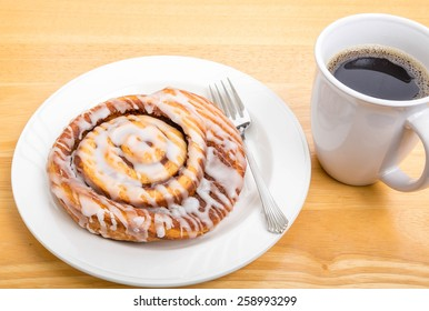 A fresh cinnamon roll on a plate with fork and a cup of coffee