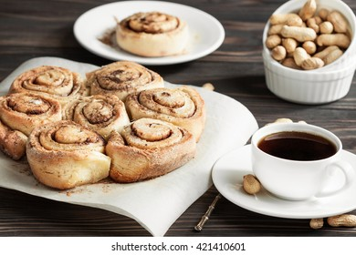 Fresh cinnamon rolls and coffee on a wooden breakfast table