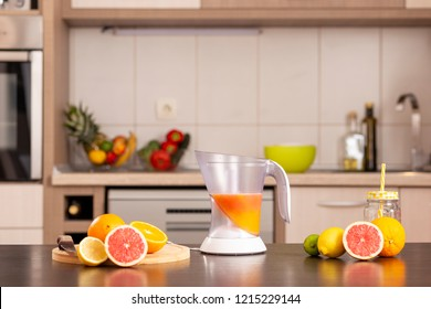 Fresh citrus fruit on a kitchen counter next to a citrus juicer