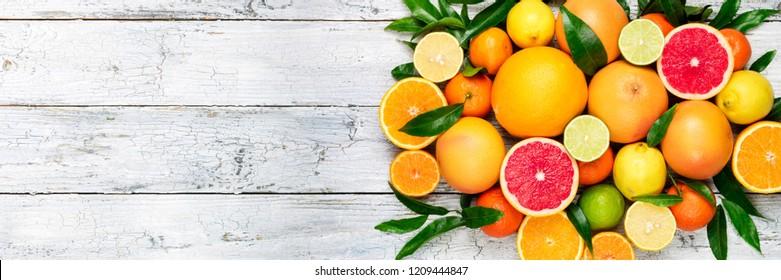 Fresh citrus fruits background. Orange, grapefruit, lemon, lime, tangerine. Mix citrus fruits with leaves. Long web format. Copy space