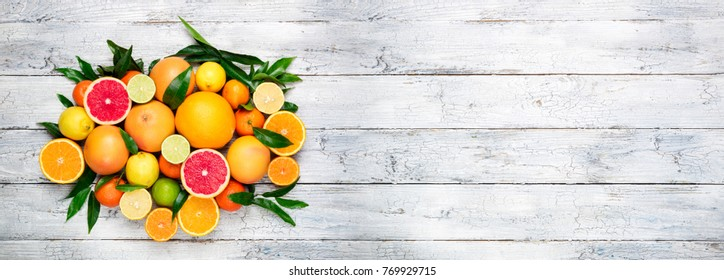 Fresh citrus fruits background. Orange, grapefruit, lemon, lime, tangerine. Mix citrus fruits with leaves. Long web format for banner. Top view