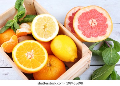 Fresh citrus fruits with green leaves in wooden box on color wooden background
