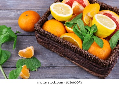 Fresh citrus fruits with green leaves in wicker basket on wooden background
