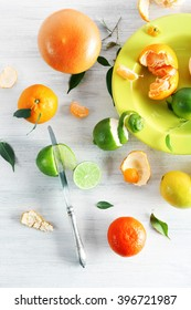 Fresh citrus fruits with green leaves on wooden table closeup