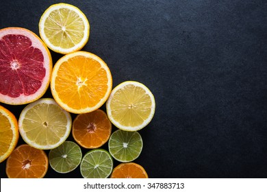 Fresh citrus fruits half cut, dark border background with copy space,from above