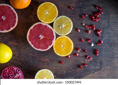 Fresh citrus fruits and pomegranate seeds on a wooden background