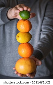 Fresh citrus fruits stack hold in man hands. Delicious juicy fruits column. Grapefruit, orange, lemons and lime pile. Healthy eating. Veganism concept