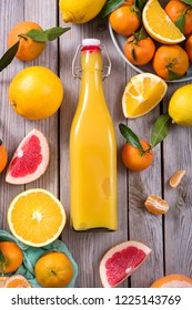 Fresh citrus juice in a bottle with different citrus fruits, flat lay, healthy vitamin drink