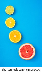 Fresh citrus slices on blue paper texture background. Top view. Lemon lime pomelo orange grapefruit slices vertical image