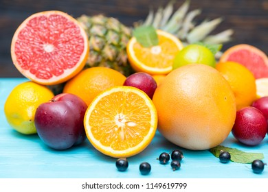 Fresh citrus and tropical fruit for a healthy diet arranged in a pile on a blue wood table with assorted citrus, plums, blueberries and pineapple