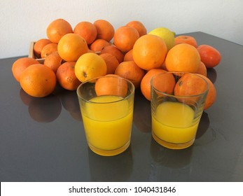 Fresh citruses, oranges and tangerines, and two glasses of fresh juice which is just prepared.