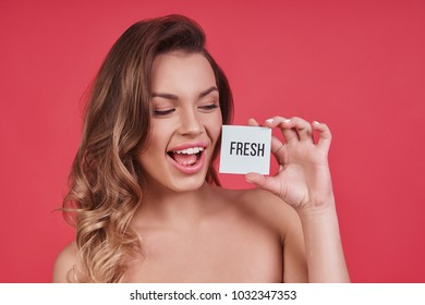 Fresh and clean.  Attractive young woman keeping mouth open and holding a small poster while standing against pink background