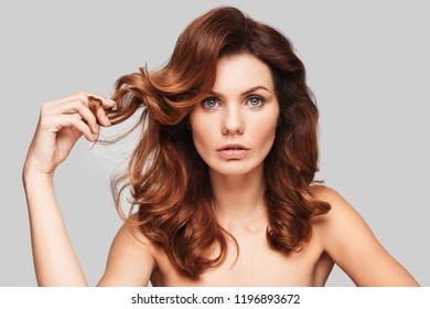 Fresh and clean. Attractive young woman looking at camera and touching her hair while standing against grey background