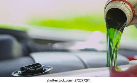 Fresh clean green oil being poured into a car engine
