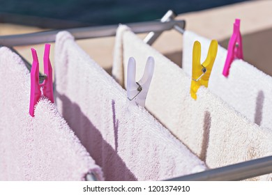 Fresh clean towels drying on washing line outdoor. Laundry hangs on the dryer. Drying clean clothes after washing, homework concept