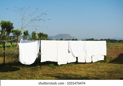 Fresh clean white bed-sheet,towel and  clothes hanging on the line  on sunny day , natural landscape background