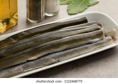 Fresh cleaned raw eels on a dish ready to cook