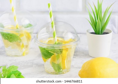 Fresh Cleansing Juicy Lemon Mint Leaf Detox Water. Lemonade Refreshment. Soft Beverage Served in Glass with Straw. Homeplant on White Table Background. Vegetarian Healthy Detox Drink