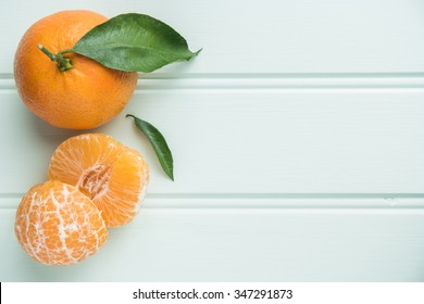Fresh clementines on wooden board with leaves. Top view with copy space.