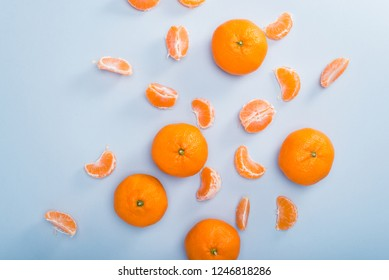 Fresh clementines scattered on blue background, top view
