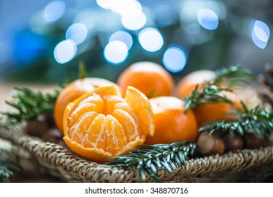 Fresh Clementines or Tangerines in the Basket on Brown Wooden Table with Xmas Lights and Tree Branches