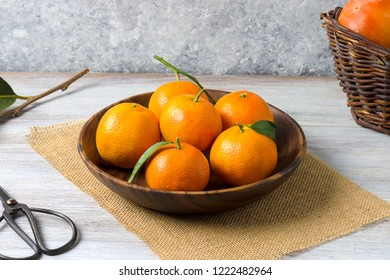 Fresh clementines in a wooden basket, on a rustic wooden background