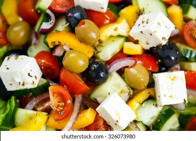 Fresh Close up Vegetable Greek Salad with Feta cheese, black and green olives, cherry tomatoes, yellow pepper, red onion, cucumber. On wooden table