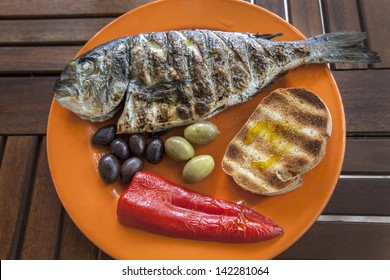 A fresh cocked fish with roasted bread, olives kalamata and pepper