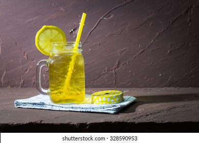 Fresh cocktail with lemon iced tea on stone table, rustic style