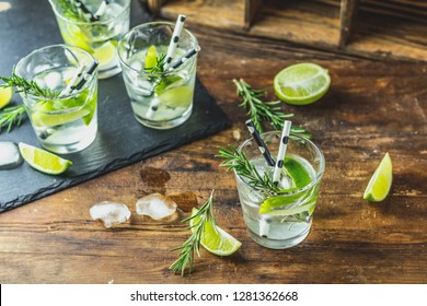 Fresh cocktail with lime, ice and rosemary, mojito cocktail in a bur on a rustic table, selective focus, shallow depth of the field.