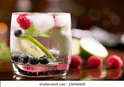 Fresh cocktail with mint and berries on the brown table
