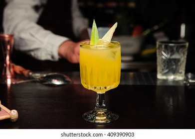 Fresh cocktail with orange and ice on bar, selective focus