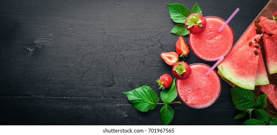 Fresh cocktail of watermelon and strawberries. Mint, ice. On a wooden board. Top view. Free space for your text.