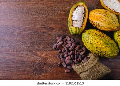 Fresh cocoa fruit with cocoa pods and cocoa beans on wooden background.