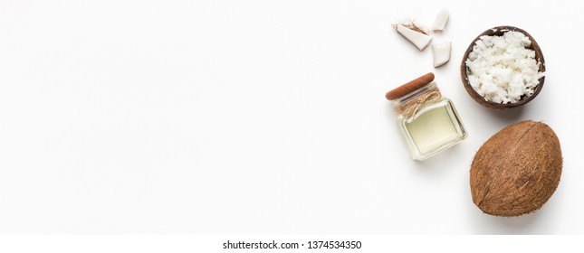 Fresh coconut, coco flesh and jar of coconut oil on white background, top view, copy space. Organic fats concept