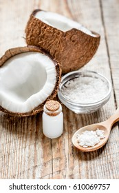 fresh coconut with cosmetic oil in jar on wooden background