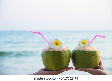 Fresh coconut in couple hands with plumeria decorated on beach with sea wave background - honeymoon couple tourist with fresh fruit and sea sand sun vacation background concept