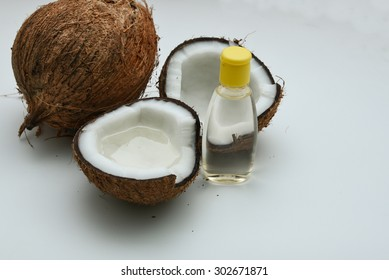 Fresh coconut cut open in half with extra clear and pure coconut oil. tropical Spa beauty exotic tropical flowers towels soap setting. Wellness & spa alternative treatment  isolated white