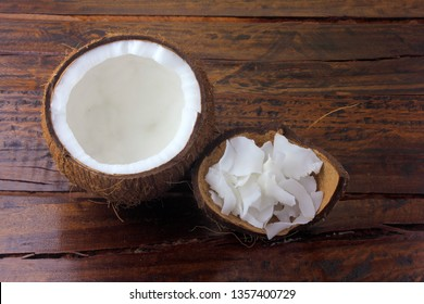 fresh coconut flakes and chips placed in bark and shell isolated on rustic wooden background