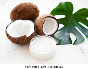 Fresh coconut oil and coconuts on a white marble background