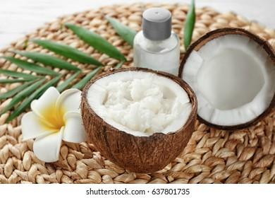 Fresh coconut oil in half of nut on wicker mat