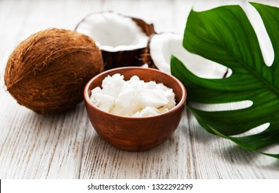 Fresh coconut oil and coconut on a white wooden table