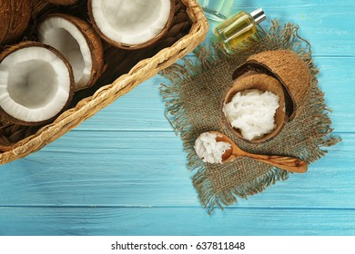 Fresh coconut oil in shell of nut and spoon on wooden table
