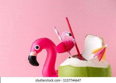 Fresh coconut on a pastel pink background with flamingo inflatable drink holder, summer vibes concept
