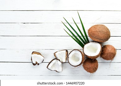 Fresh coconut on a white wooden background. Tropical Fruits. Nut. Top view. Free space for your text.