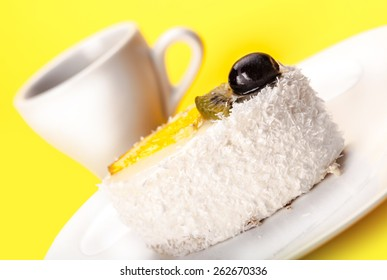 fresh coconut slice of cake and a cup on a yellow background